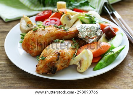 Fried chicken legs with herbs and spices, vegetables for garnish - stock photo