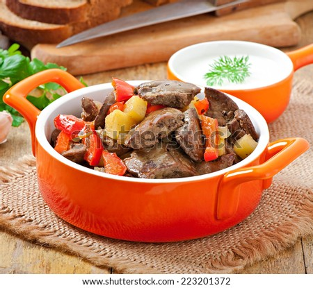 Fried chicken liver with apples and paprika - stock photo