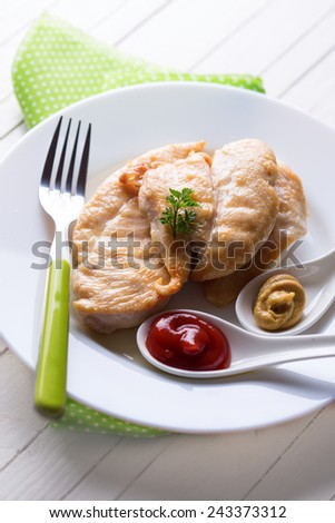 Fried chicken meat on plate with sauces on wooden background. Selective focus.  - stock photo