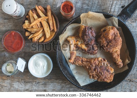 Fried chicken meat with buttermilk and french fries on wooden background - stock photo