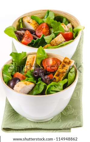 Fried chicken salad with cherry tomatoes and black olives in white bowls