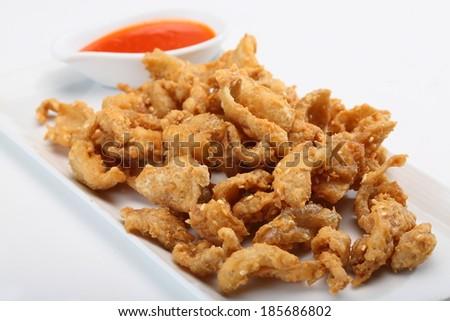 Fried chicken skin served on white dish  - stock photo