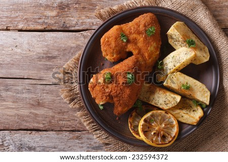 Fried chicken wings dipped in batter closeup with garnish on a plate on the old table top view  - stock photo