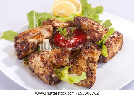 fried chicken wings in sauce with lemon and tomato sauce