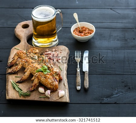 Fried chicken wings on rustic serving board, spicy tomato sauce, herbs and mug of light beer over black wooden backdrop, copy space, selective focus - stock photo