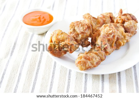 Fried chicken with skewer on white dish and chilli sauce. - stock photo