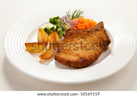Fried chop pork, chips and vegetable salad - stock photo