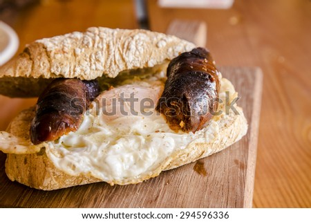 Fried chorizo sausage and egg with homemade rustic bread sandwich - stock photo