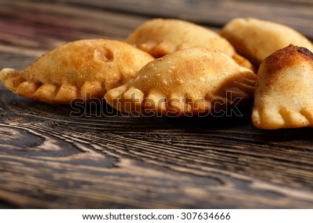 Fried colombian empanadas on wooden table. Savory stuffed patties also known as pastel,pate or pirozhki - stock photo