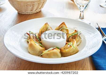 Fried dumplings with sour cream sauce - stock photo