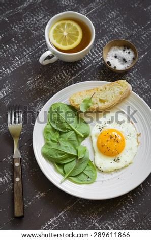 fried egg and fresh spinach on a white plate on a dark background - stock photo