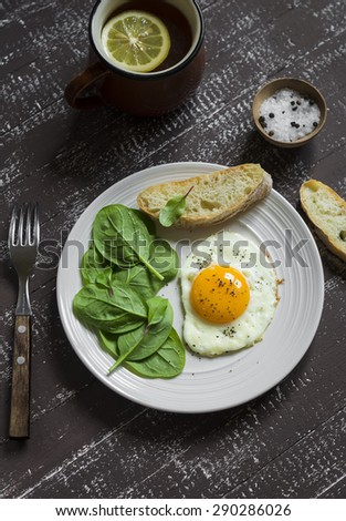 fried egg and fresh spinach on a white plate on a dark wooden background - stock photo