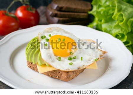 Fried egg, avocado and cheese on toast - stock photo