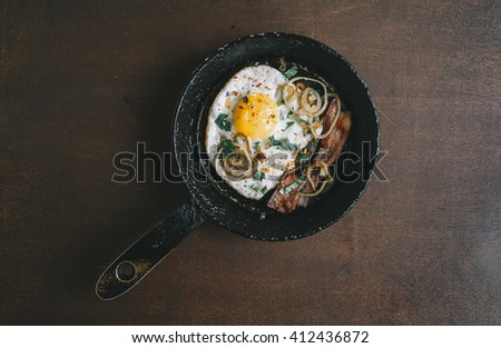 fried egg, bacon, onion rings, parsley - tasty Breakfast or snack, in the old pan on a dark wooden background. Top view. - stock photo
