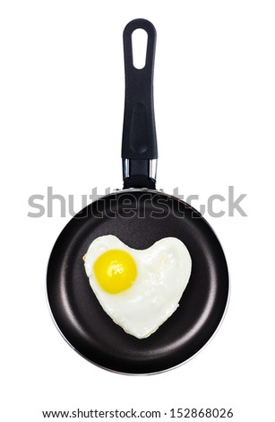 Fried egg heart shape in a pan isolated on white background. - stock photo