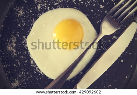Fried egg in a frying pan and cutlery - stock photo