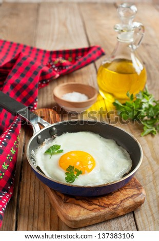 Fried egg in a frying pan for breakfast - stock photo