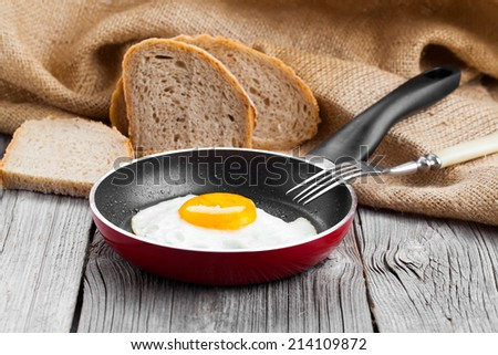 Fried egg in a frying pan, on an old wooden table - stock photo