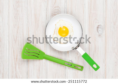 Fried egg in a frying pan. Top view over white wooden table  - stock photo