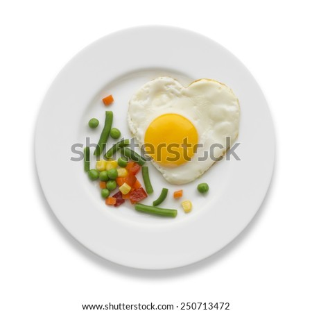 Fried egg in a shape of the heart and some vegetables on a white plate isolated - stock photo