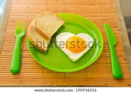 Fried egg in heart shape on green plastic plate - stock photo