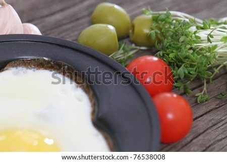 Fried egg in heart-shaped form with cress, tomato, garlic, olives