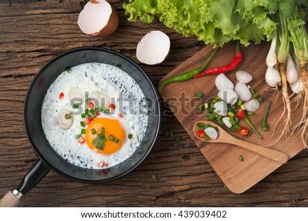fried egg in pan and vegetable on wood background, prepared food for breakfast. - stock photo