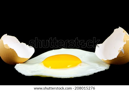 Fried egg isolated on a black background and shells