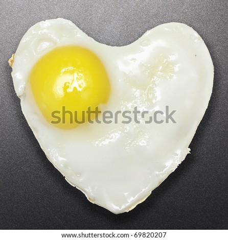 Fried egg like heart on frying pan. - stock photo