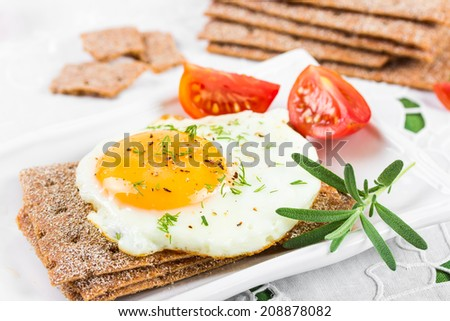 Fried egg on crisp bread and tomatoes. - stock photo
