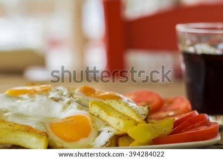 fried egg,  potatoes fries, tomatoes and a glass of drink. Breakfast  in Greece - stock photo