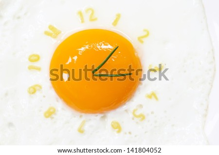 Fried egg sunny side up in form of a clock - stock photo