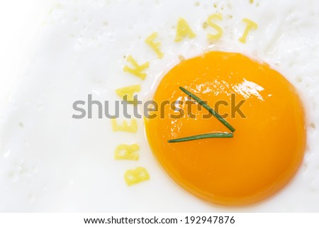 Fried egg sunny side up in form of a clock with noodle letters for breakfast - stock photo