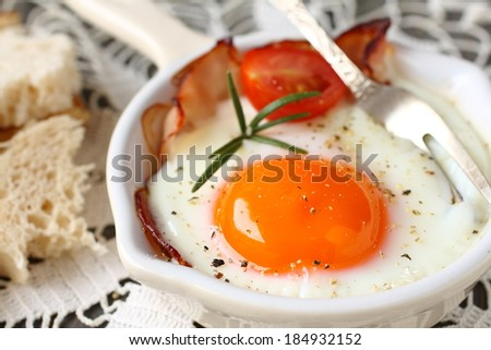Fried egg with bacon, tomato, rosemary and sliced bread - stock photo