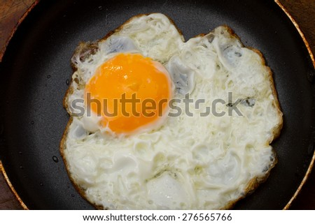 Fried Egg with pan, isolated on wood background - stock photo