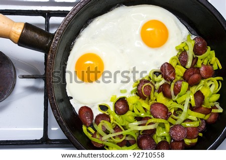 Fried egg with sausage and leek - stock photo