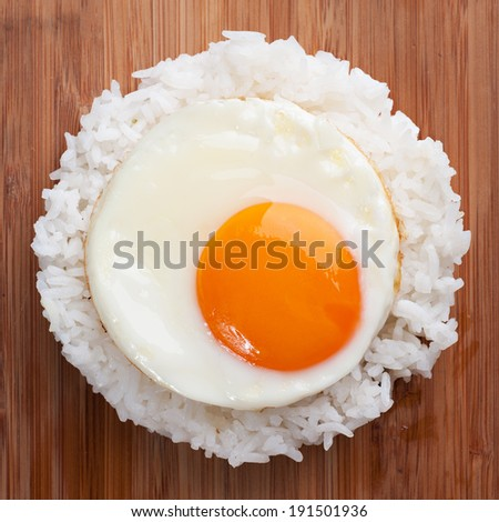 fried egg with steam rice on wooden table - stock photo