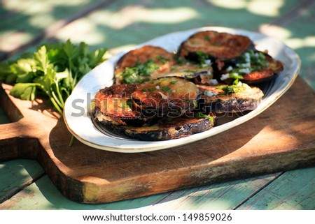 fried eggplant with freshly grated garlic and parsley  - stock photo