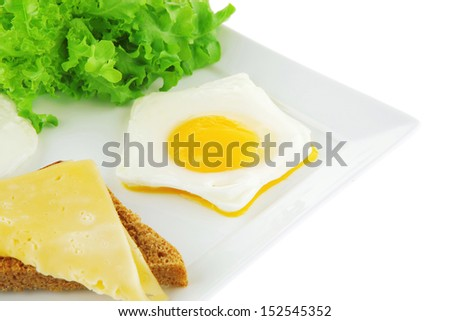 fried eggs and gold cheese on white plate
