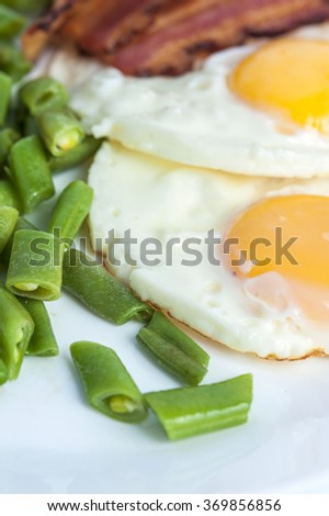 Fried eggs, bacon, green beans on light background. English breakfast. Vertical view. Focus on beans.