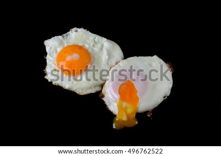 Fried eggs close up on a black background. Fried egg isolated on black.
