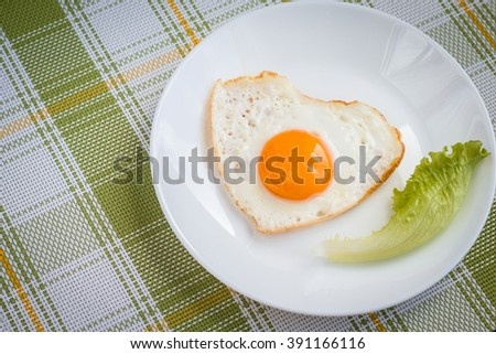 Fried eggs in form of heart. Healthy breakfast of fresh vegetables and eggs - stock photo