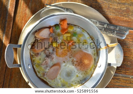 Fried eggs in pan with hot-dog and vegetable on wooden background.
