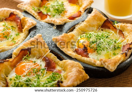 Fried eggs in puff pastry in ham, baked with cheese and topped with microgreens, fresh juice from oranges and eggs stuffed with chocolate - stock photo