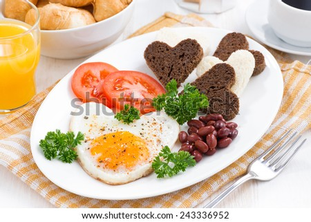 fried eggs in the form of heart for breakfast Valentine's Day on white plate, horizontal - stock photo