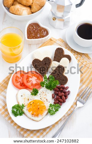 fried eggs in the form of heart for breakfast Valentine's Day, vertical, top view, close-up - stock photo