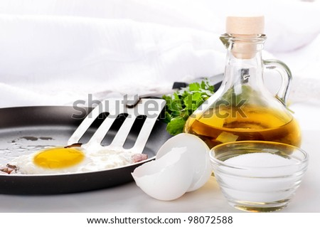 Fried eggs on a frying pan with olive oil and an egg shell