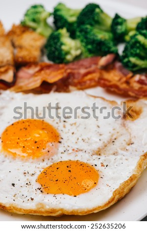 Fried Eggs on a plate with bacon, croutons and broccoli. Selective focus on fronted egg yolk.
