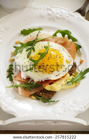 Fried eggs on toast with prosciutto. - stock photo
