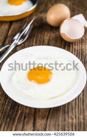 Fried Eggs on vintage wooden background (selective focus; close-up shot) - stock photo